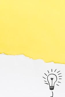 Papel amarelo rasgado com lâmpada de mão desenhada no fundo branco