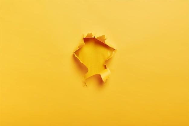 Papel amarelo rasgado e rasgado com furo no centro