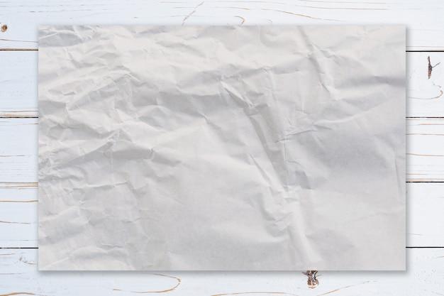 Papel amarrotado na textura branca do fundo da pintura de madeira com espaço do café.