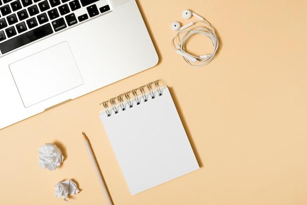 Papel amassado; bloco de anotações; lápis; fone de ouvido; e laptop sobre fundo bege