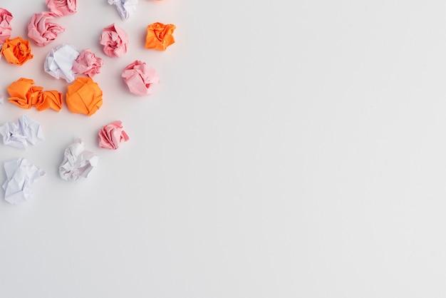 Papel amassado colorido no canto do fundo branco