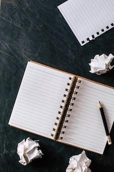 Papel amassado com caderno e lápis sobre fundo preto