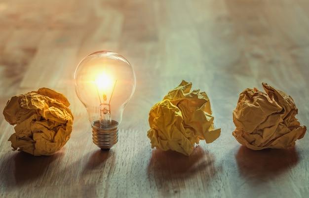 Papel amassado com lâmpada de pé na madeira para bom novo conceito de idéia