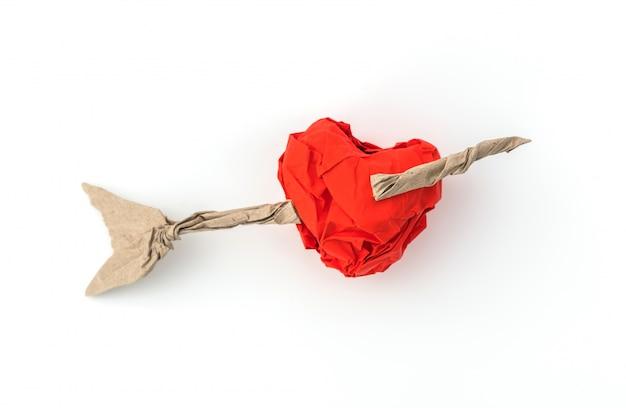 Papel amassado coração no fundo branco.