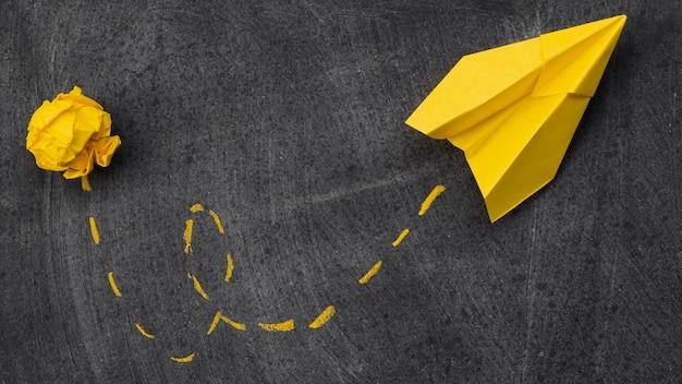 Papel amassado e avião de papel com metáfora de idéia de trilha