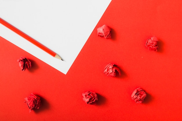 Papel amassado vermelho sobre fundo de papel duplo com lápis