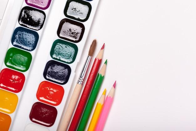 Papel, aquarelas, pincel e algumas coisas de arte close-up vista superior