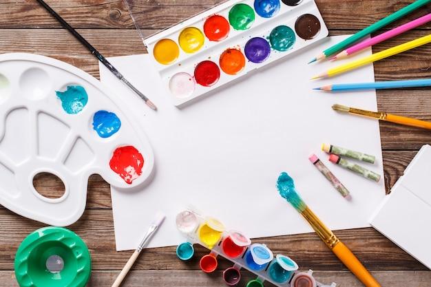 Papel, aquarelas, pincel e algumas coisas de arte na mesa de madeira