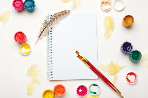 Papel, aquarelas, pincel e algumas coisas de arte na vista de uma mesa