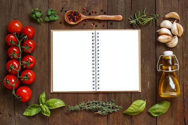 Papel artesanal com borda de vegetais, ervas e azeite em uma mesa de madeira, vista de cima com espaço de cópia