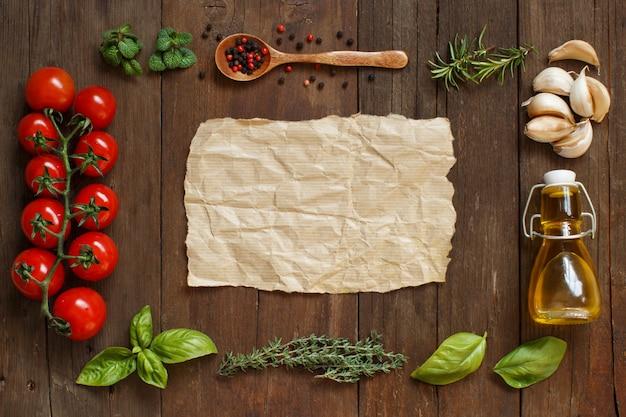 Papel artesanal com borda de vegetais, ervas e azeite na vista superior da mesa de madeira