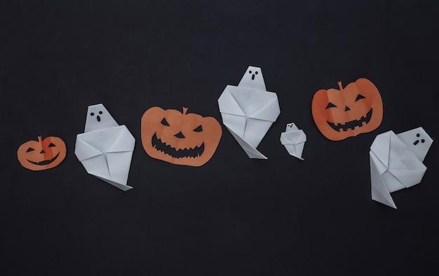 Papel artesanal cortado decoração de halloween em fundo preto. abóbora de halloween e fantasmas