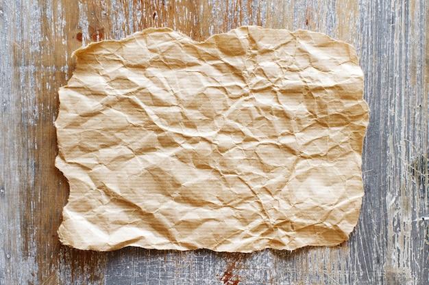 Papel artesanal em branco em uma vista de mesa de madeira
