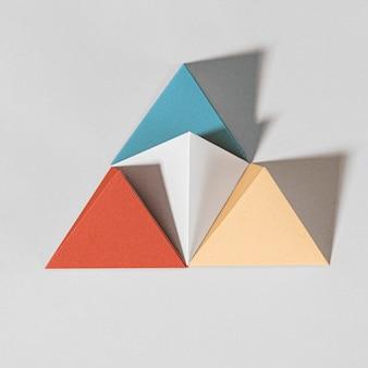 Papel artesanal em pirâmide colorida 3d em um fundo cinza