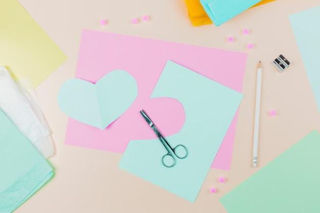 Papel azul de forma de coração com tesoura; lápis e apontador em pano de fundo bege