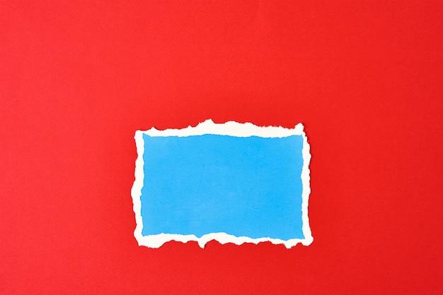 Papel azul rasgado com bordas rasgadas isoladas em vermelho