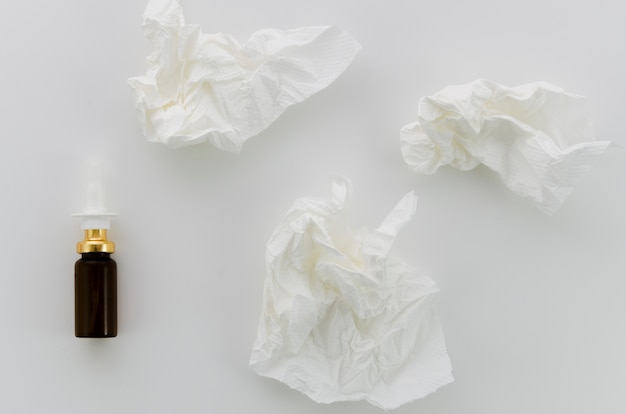 Papel branco amassado e frasco conta-gotas em fundo branco