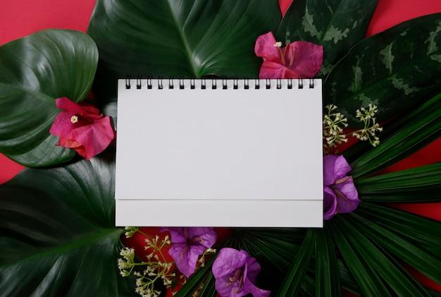 Papel branco com espaço para texto ou imagens sobre fundo vermelho e folhas tropicais e flores