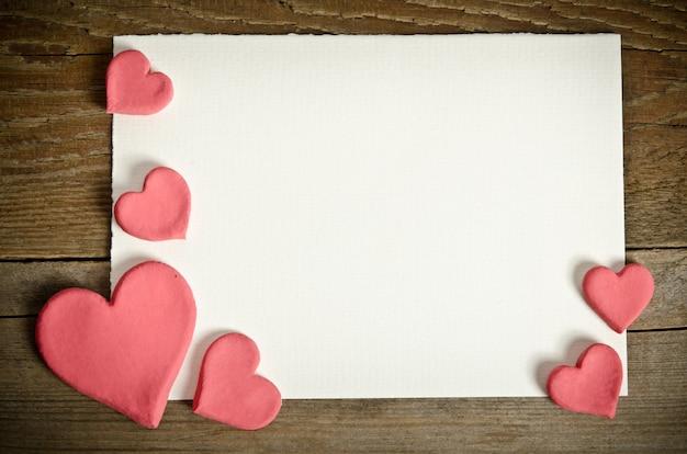 Papel branco com pequenos corações rosa sobre uma mesa de madeira