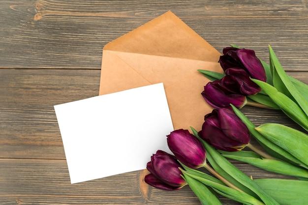 Papel branco e envelope para escrever e flores de tulipa em um fundo de madeira, espaço para texto