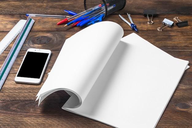 Papel branco em branco; celular e artigos de papelaria na mesa de madeira