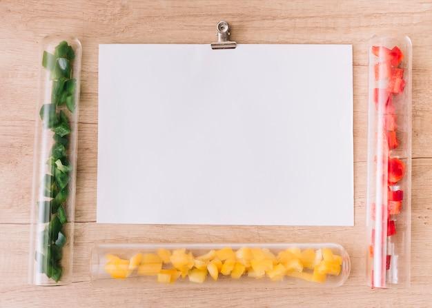 Papel branco em branco cercado com tubos de ensaio transparentes com fatias de verde; pimentão amarelo e vermelho