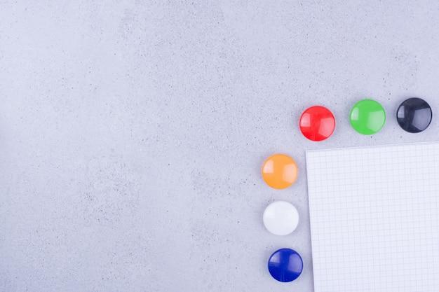 Papel branco em branco com alfinetes coloridos ao redor