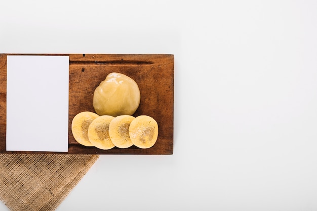 Papel branco em branco com coalhada de limão e biscoitos na bandeja de madeira