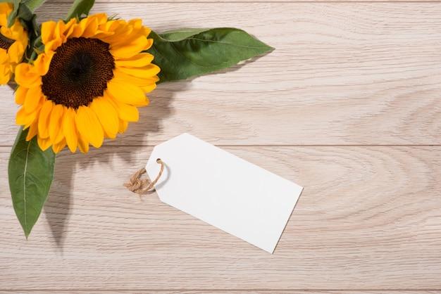 Papel branco em branco com flores coloridas em fundo de madeira. vista do topo. brincar