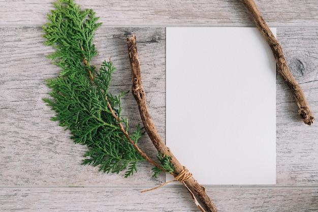 Papel branco em branco com galho de cedro e filial em plano de fundo texturizado de madeira