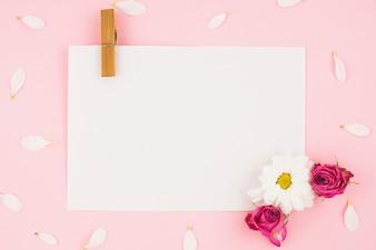 Papel branco em branco com prendedor de papel e flores sobre fundo rosa