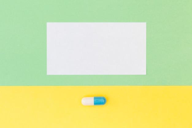 Papel branco em branco e única cápsula em fundo verde e amarelo