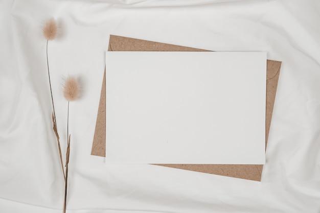 Papel branco em branco em envelope de papel pardo com flor seca de cauda de coelho em pano branco