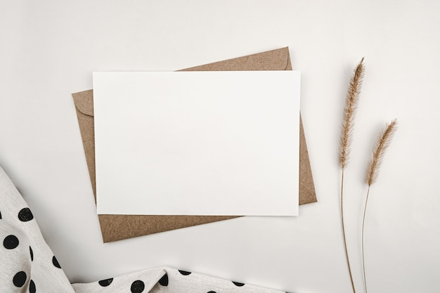 Papel branco em branco em envelope de papel pardo com flor seca de rabo de raposa eriçada e pontos pretos de pano branco