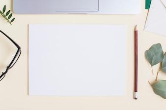 Papel branco em branco; lápis; Óculos; folhas e laptop no pano de fundo bege