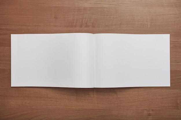 Papel branco em branco sobre a mesa de madeira
