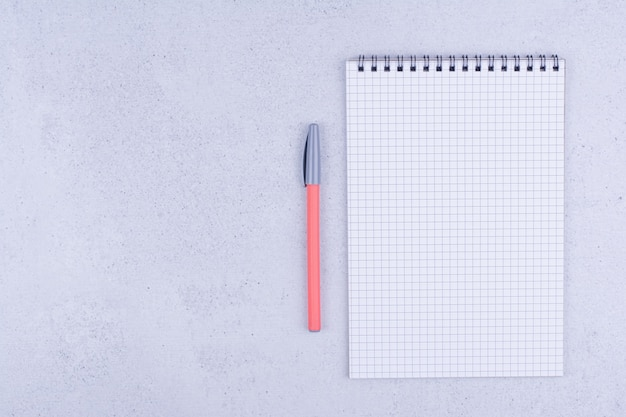 Papel branco em branco xadrez com caneta na superfície cinza