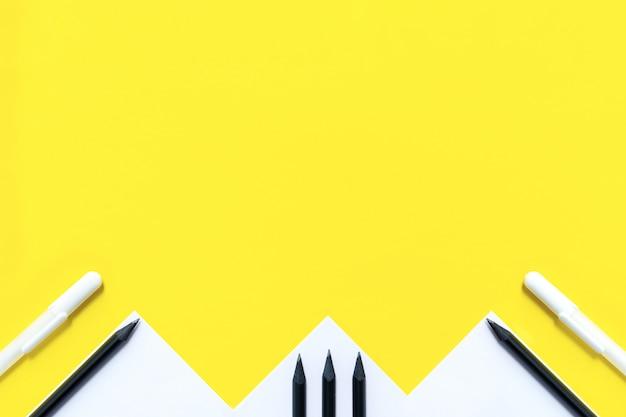 Papel branco, lápis preto e canetas brancas são dispostos aleatoriamente em amarelo.