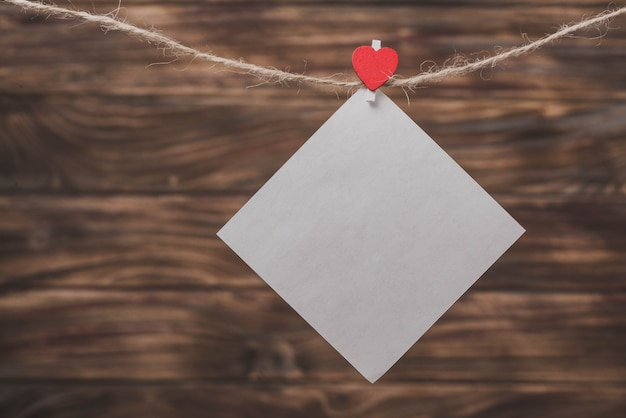Papel branco pendurado por uma corda com um clipe com um coração