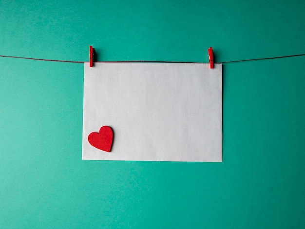 Papel branco que pesa sobre uma corda vermelha e é preso por dois prendedores de roupa e tem um coração vermelho sobre um fundo verde. um modelo para o seu projeto para o dia dos namorados
