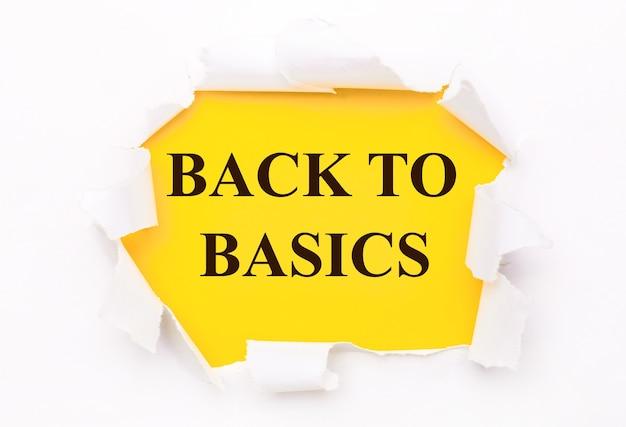 Papel branco rasgado repousa sobre uma superfície amarela brilhante com o texto voltar ao básico