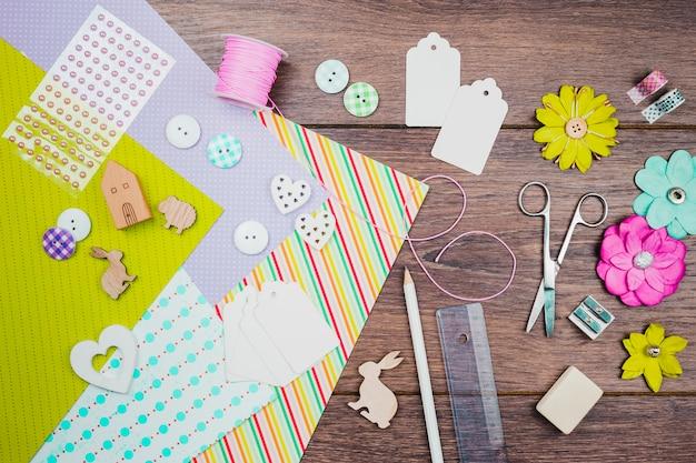Papel colorido; botões; flores de papel; tag; animais de recorte de madeira e papelaria na mesa de madeira
