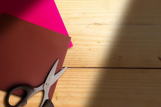 Papel colorido com tesoura em fundo de madeira
