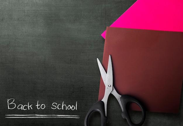 Papel colorido com uma tesoura com um fundo preto. conceito de volta às aulas