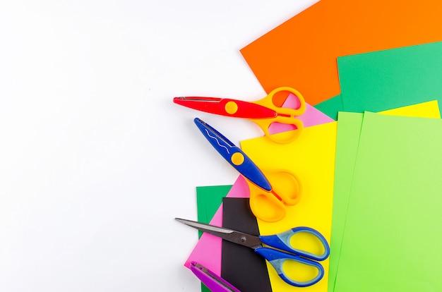 Papel colorido com uma tesoura para crianças em um copyspace branco