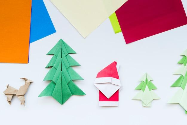 Papel colorido e árvore de natal artesanal; rena; origami de papel de papai noel isolado no fundo branco