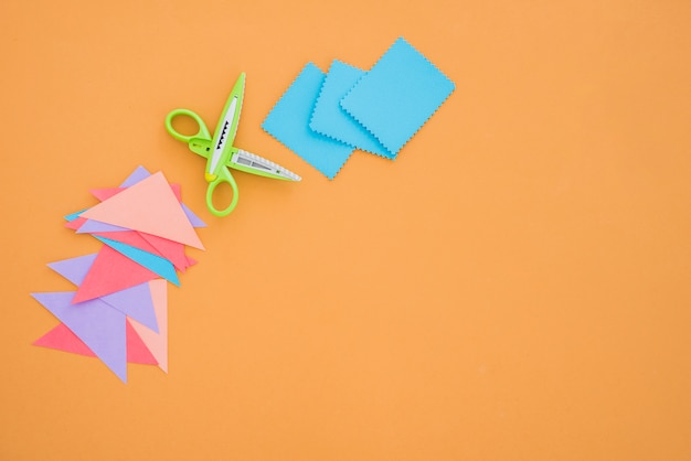 Papel colorido e tesoura em pano de fundo colorido