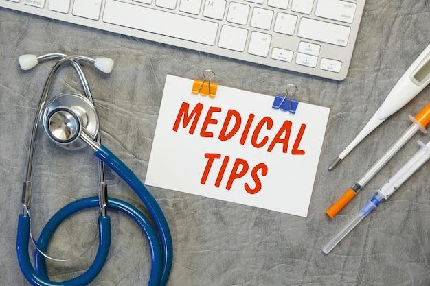 Papel com dicas médicas na mesa do escritório, estetoscópio e teclado, vista superior