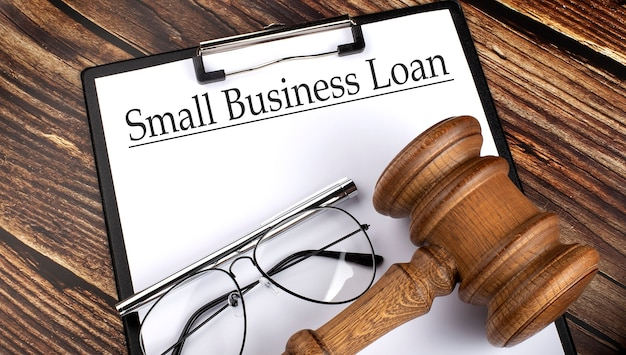 Papel com empréstimo de pequenas empresas com martelo, caneta e óculos o fundo de madeira