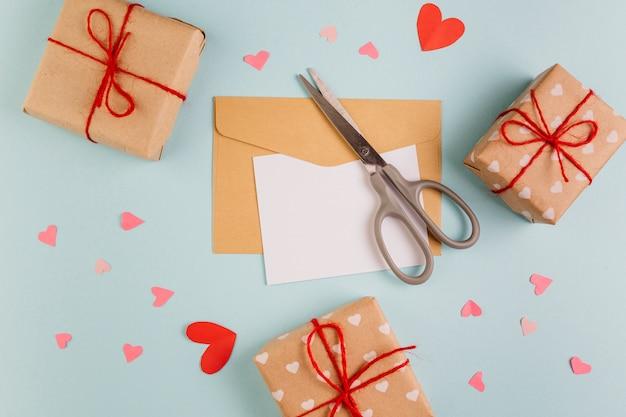 Papel com pequenas caixas de presente e tesoura